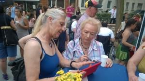 Ulla Brede-Hoffmann und eine Bürgerin probieren Freifunk aus
