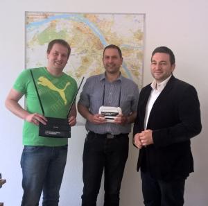 Erik Donner (l.) und Florian Altherr (r.) übergeben den Freifunk-Router an Ortsvorsteher Johannes Klomann (m.)